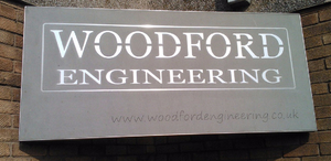 New Sign - polished stainless steel inlaid in Forest Pennant stone.